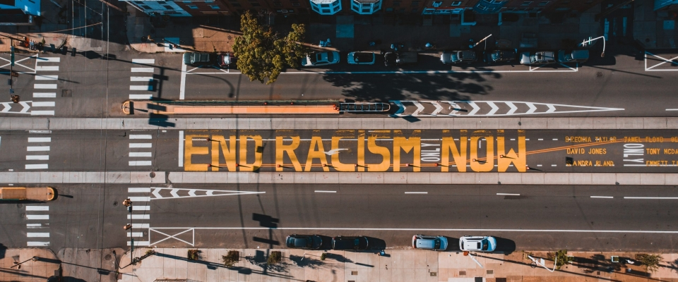 """A picture of a street with """"End Racism Now"""" painted in yellow blocks."""