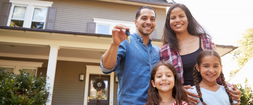 Portrait,Of,Family,Holding,Keys,To,New,Home,On,Moving